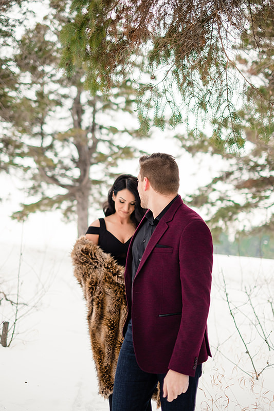 couple walking int he snow for engagement photos Birds Hill Park