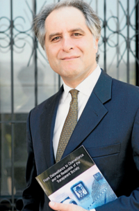 Dr M G Michael with his book  From Dataveillance to Uberveillance  and the Realpolitik of the Transparent Society . Picture: ANDY ZAKELI