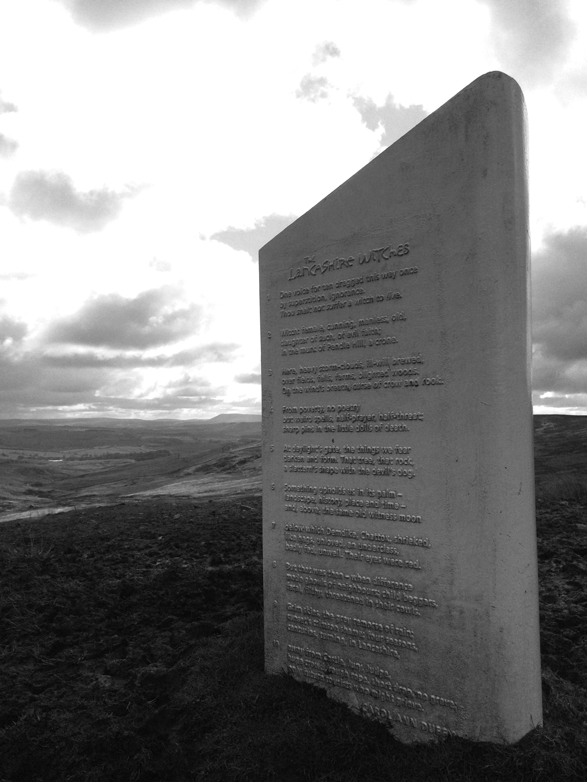 The Lancashire Witches 400 marker in Croasdale with the dark shadow of Pendle in the background.