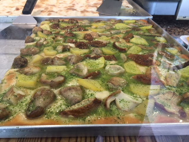Focaccia with mushrooms and potatoes topped with a green sauce.
