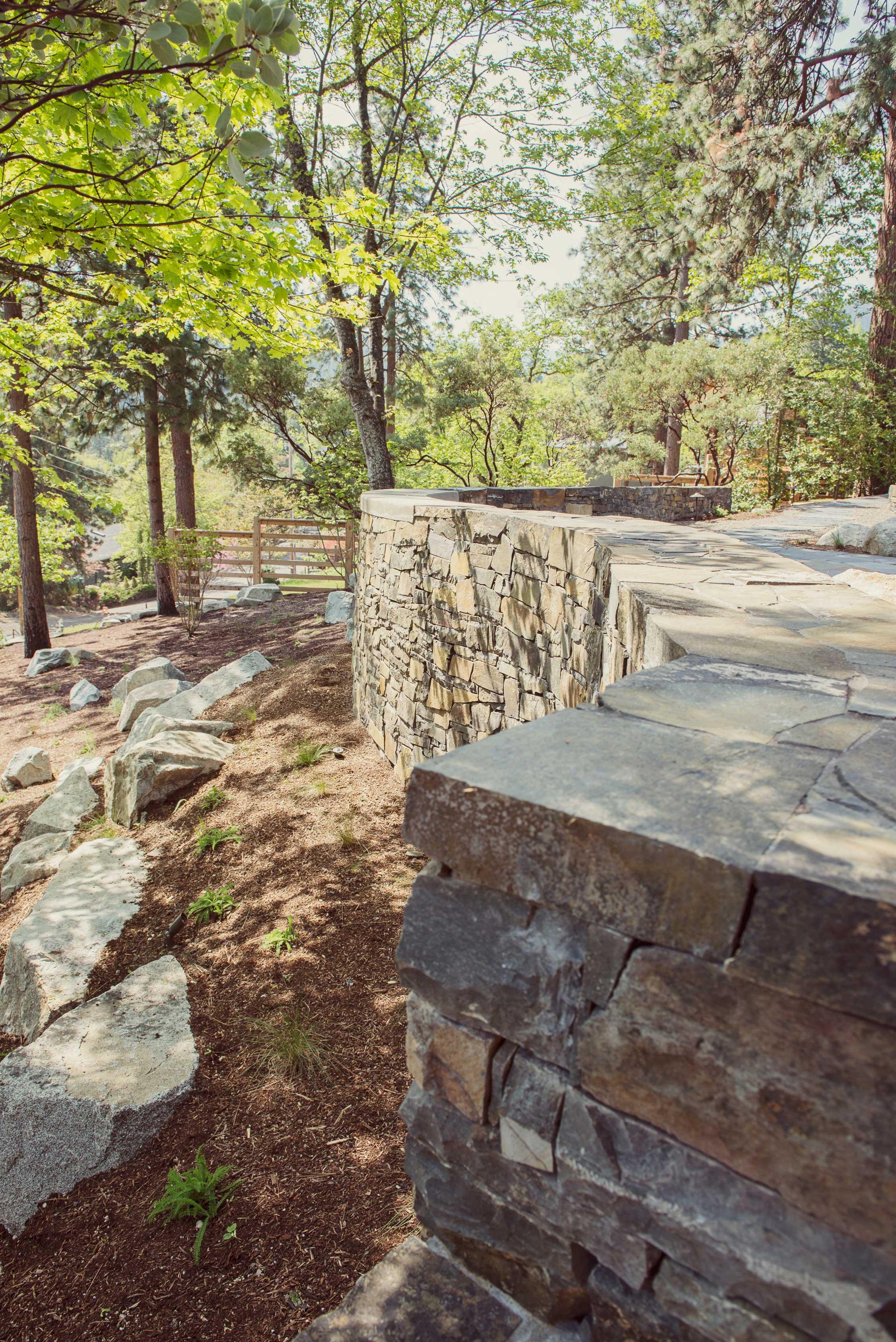 hillside retention + rock retaining wall + granite boulder sparse modern landscaping + horizontal slat wood fencing