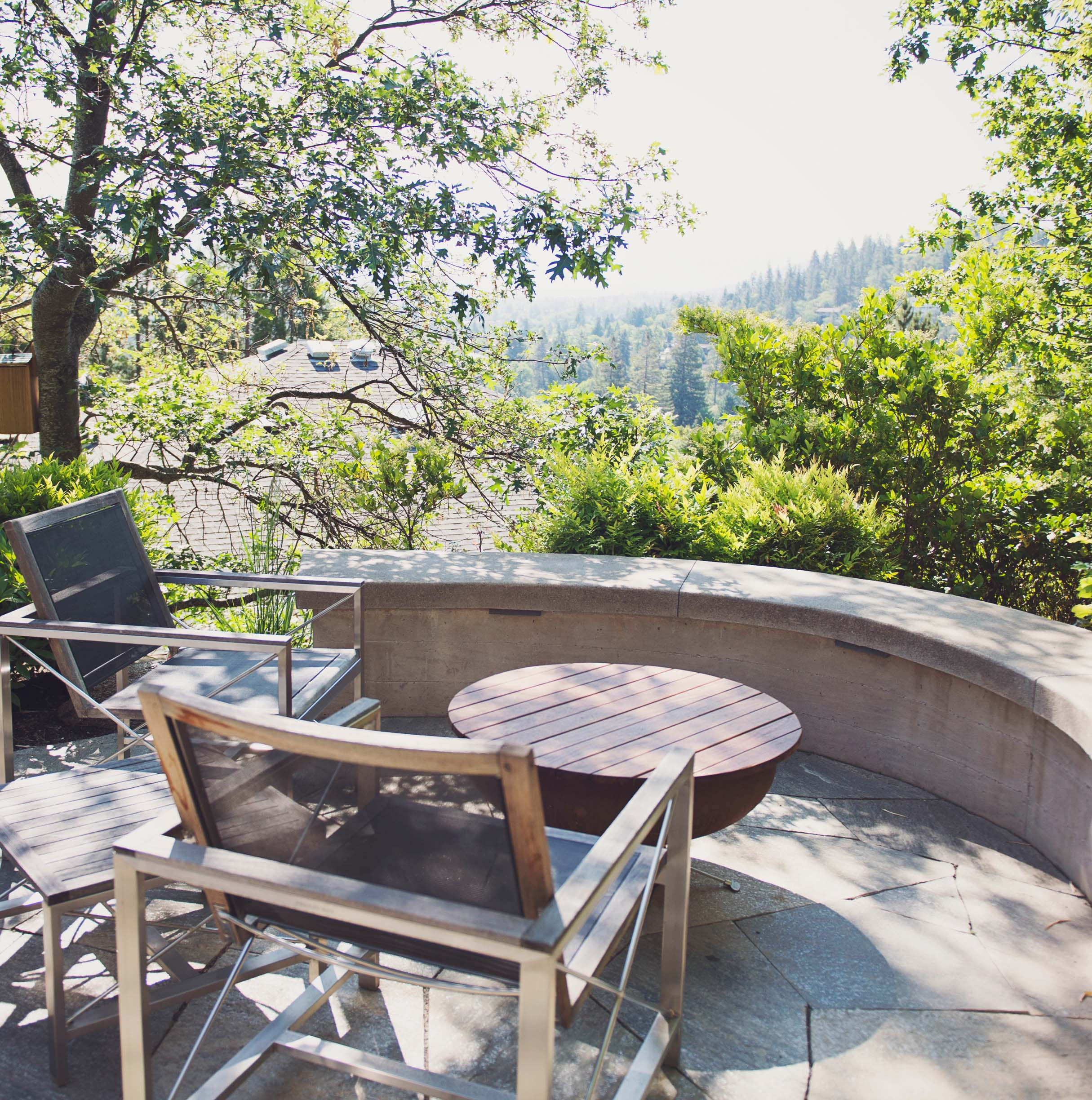 Outdoor living room + curved concrete slab wall seating + modern wood outdoor furniture + fire pit cover + recycled steel fire pit + backyard flagstone patio