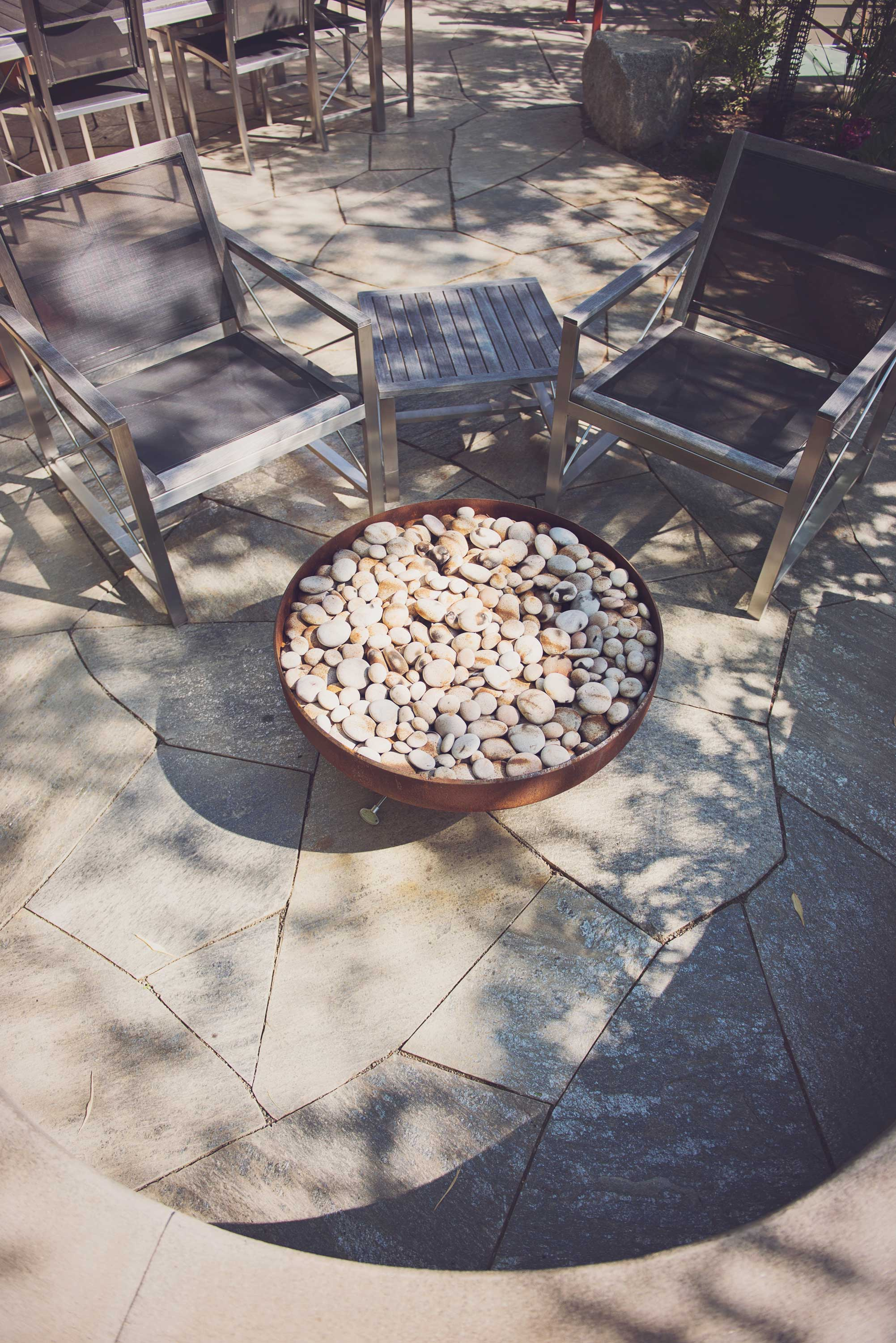 Modern Steel Fire Table with Round Fire Stones and Flagstone Patio Design.jpg