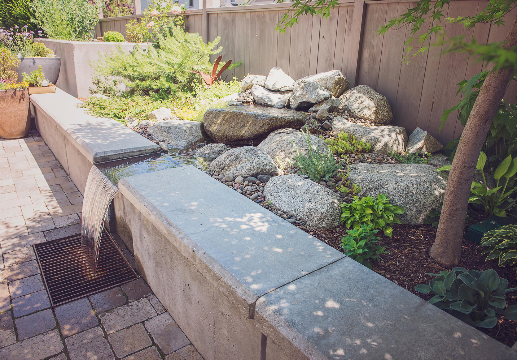 concrete bench seating + steel grate + granite boulder water feature built in + backyard relaxation
