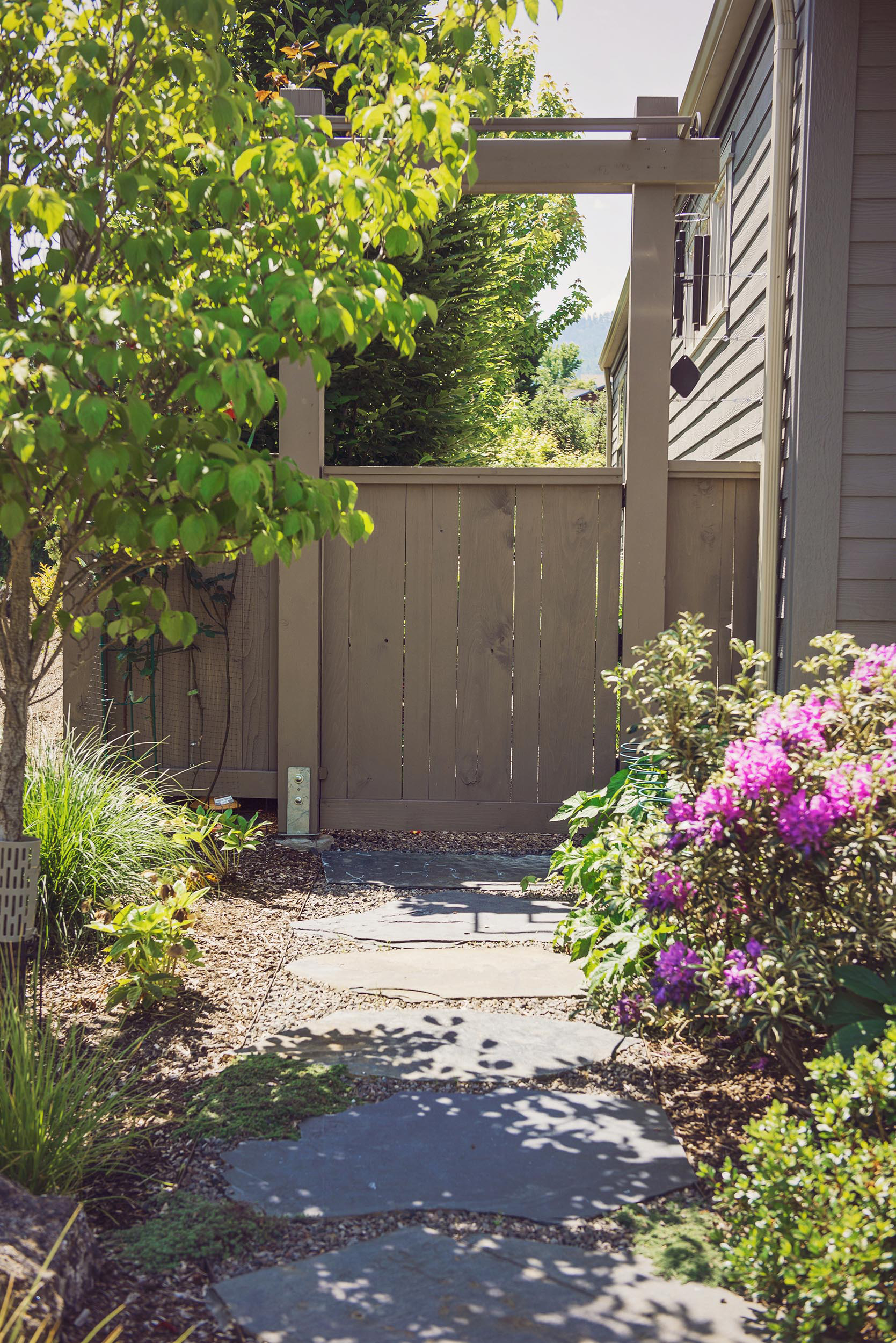 Gate + arbor + side yard entrance + flagstone pathway + crushed basalt path + bunch grass + rhododendron purple + sustainable landscaping