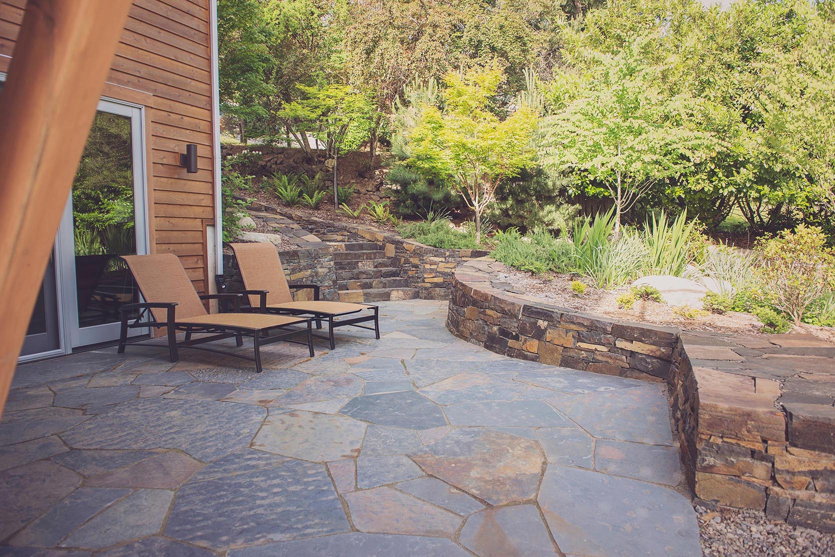 flagstone patio + locally quarried basalt stacked walls + ledgestone stairway + modern outdoor lounge + modern perennial garden + crushed basalt path
