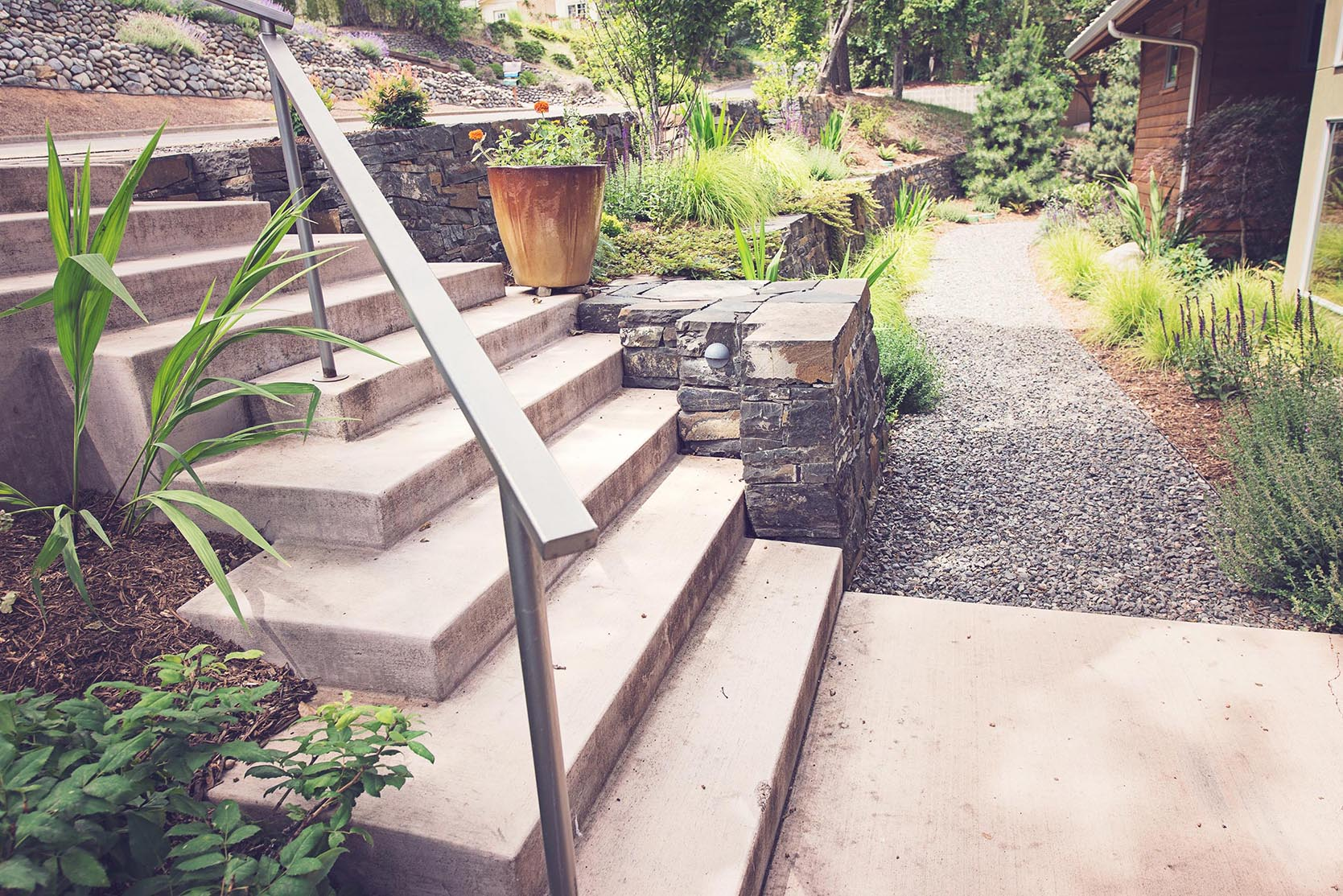 modern formed concrete descending entry stairs + concrete landing + minimalistic steel railing + stacked basalt retaing walls + modern perennial gar