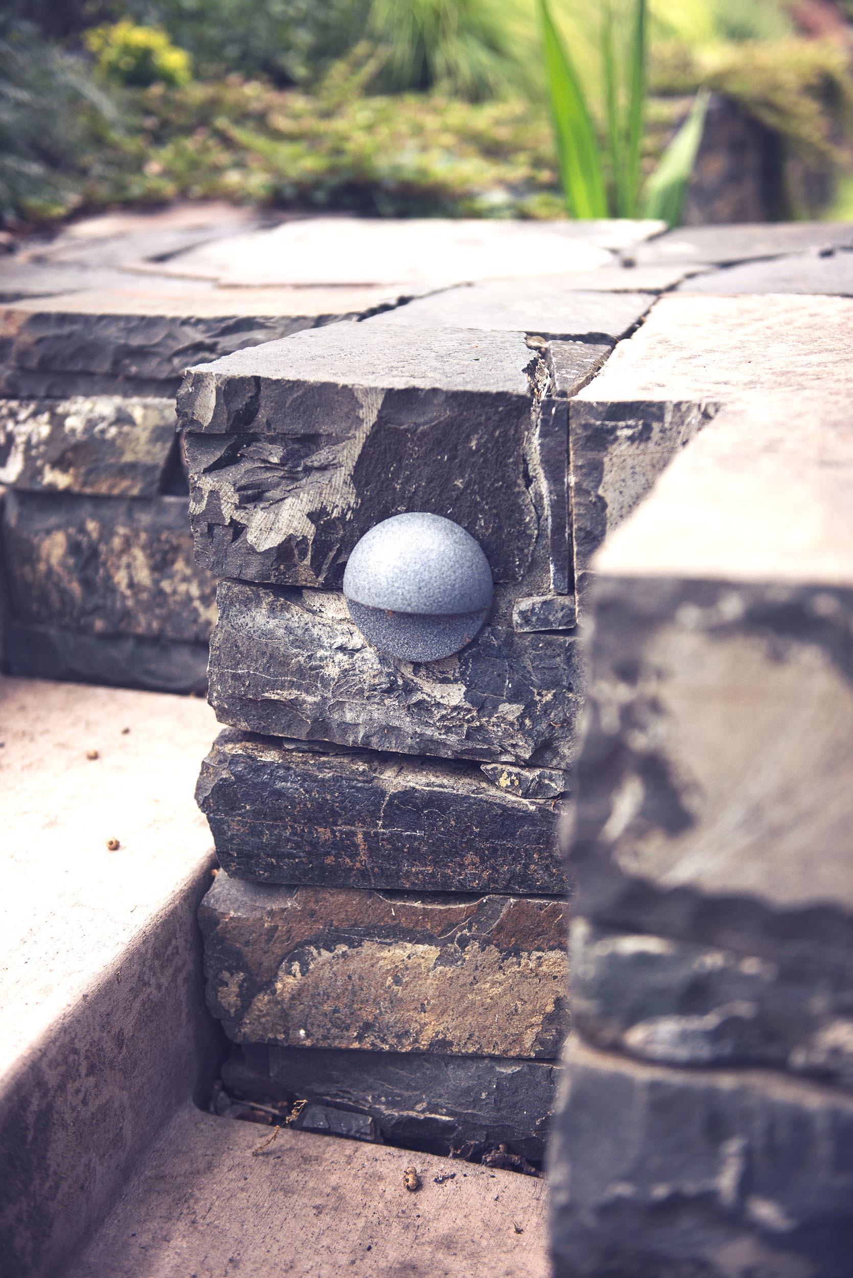 stacked basalt wall + concrete stairs + lighting + modern landscape architecture + perennial garden