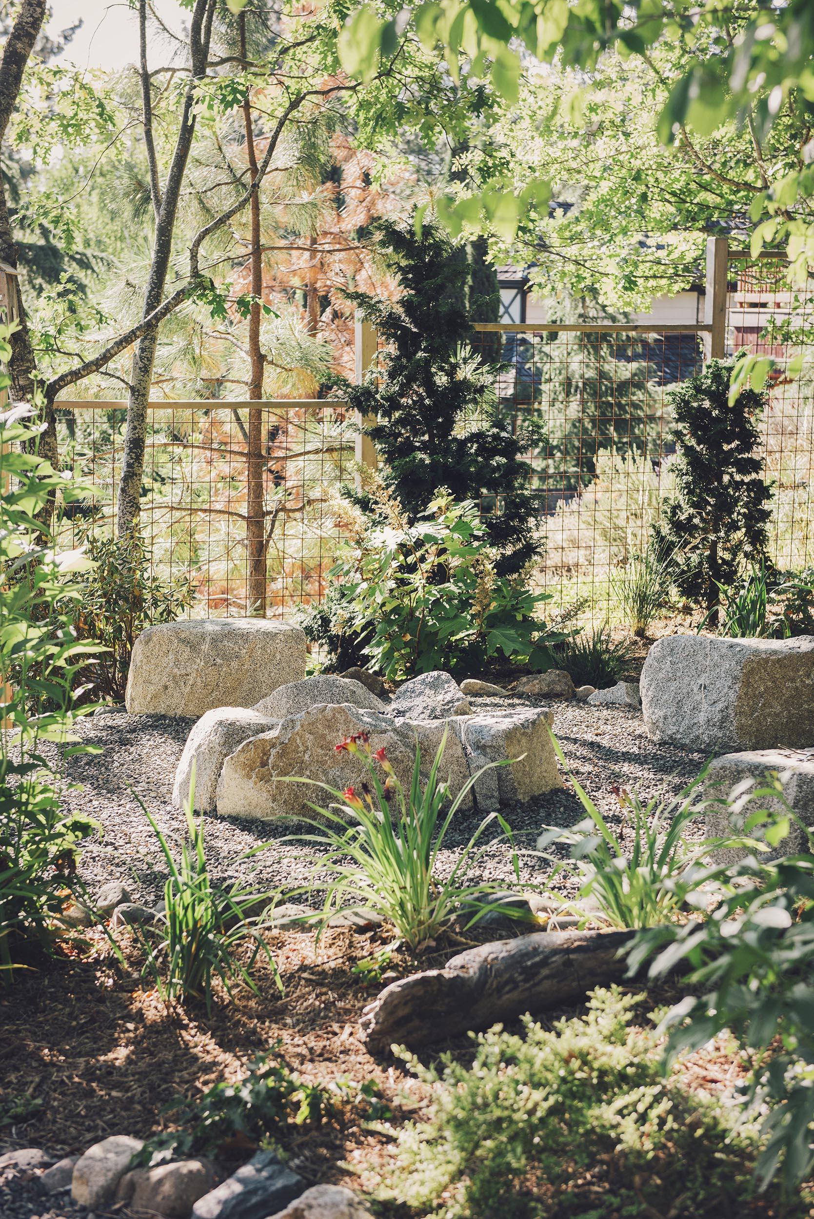 Boulder + Seating Area + crushed basalt gravel + steel wire mesh + cedar fencing + oaks backyard + granite fire pit + woodland perennial landscaping