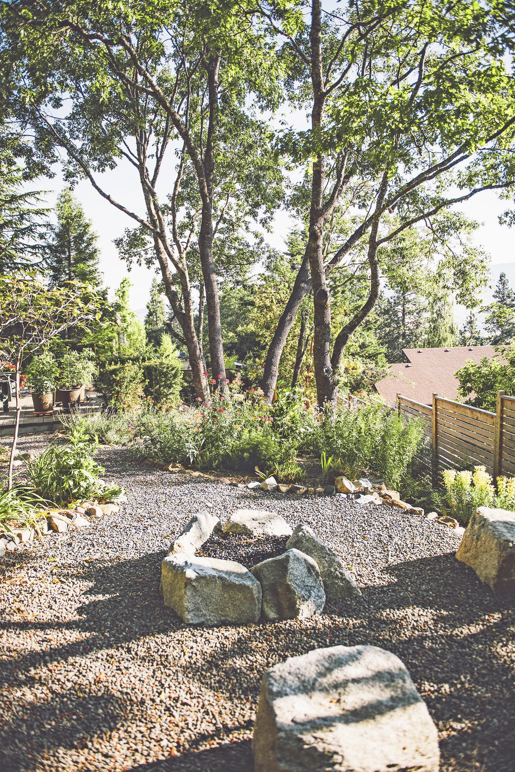 granite boulder fire pit + crushed basalt gravel paths + locally quarried rock + colorful perennial flower garden + oak canopy + modern slatted priva