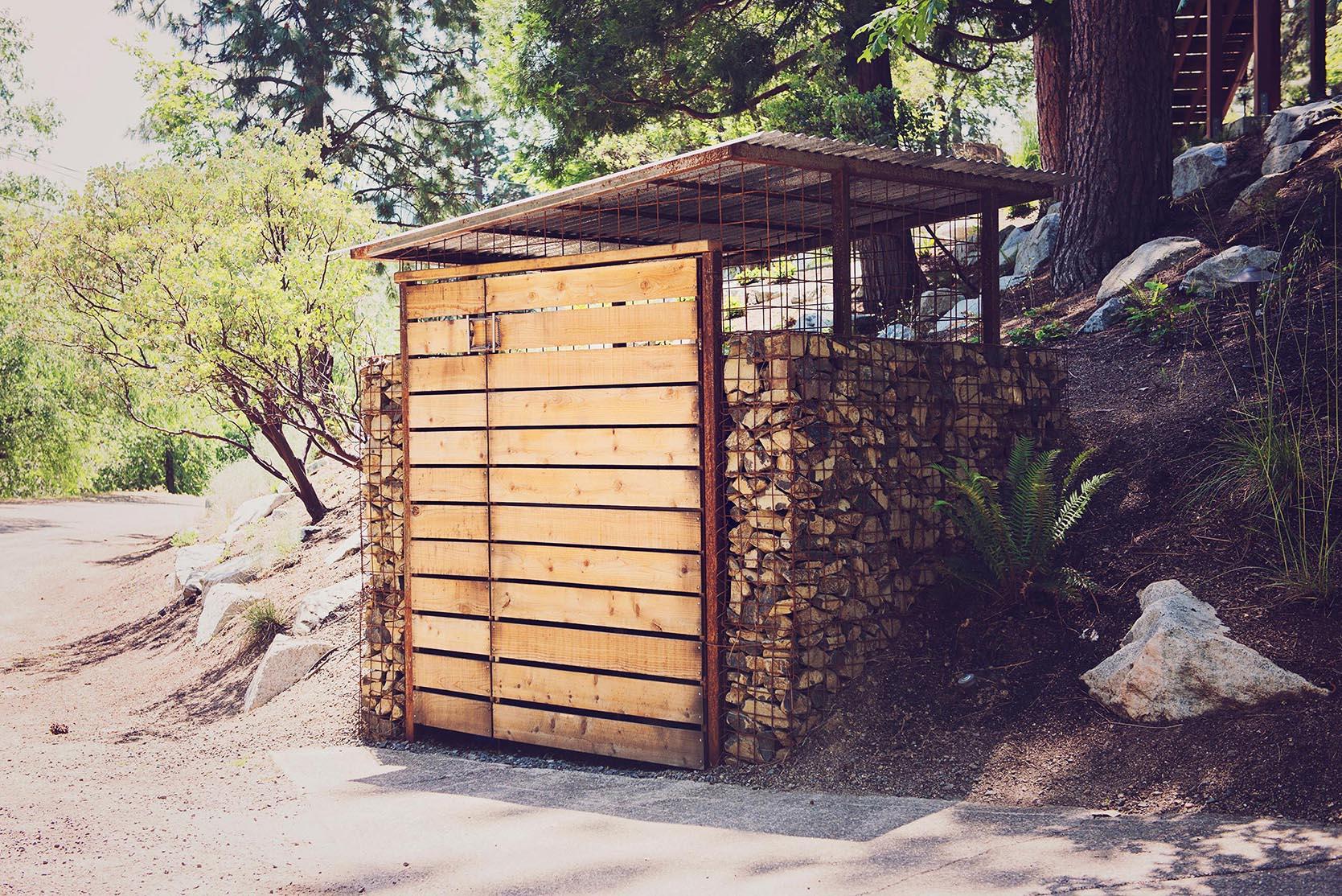 gabion + corrugated aluminum storage shed + horizontal slatted cedar door + steel mesh + modern curb side storage + landscape architecture