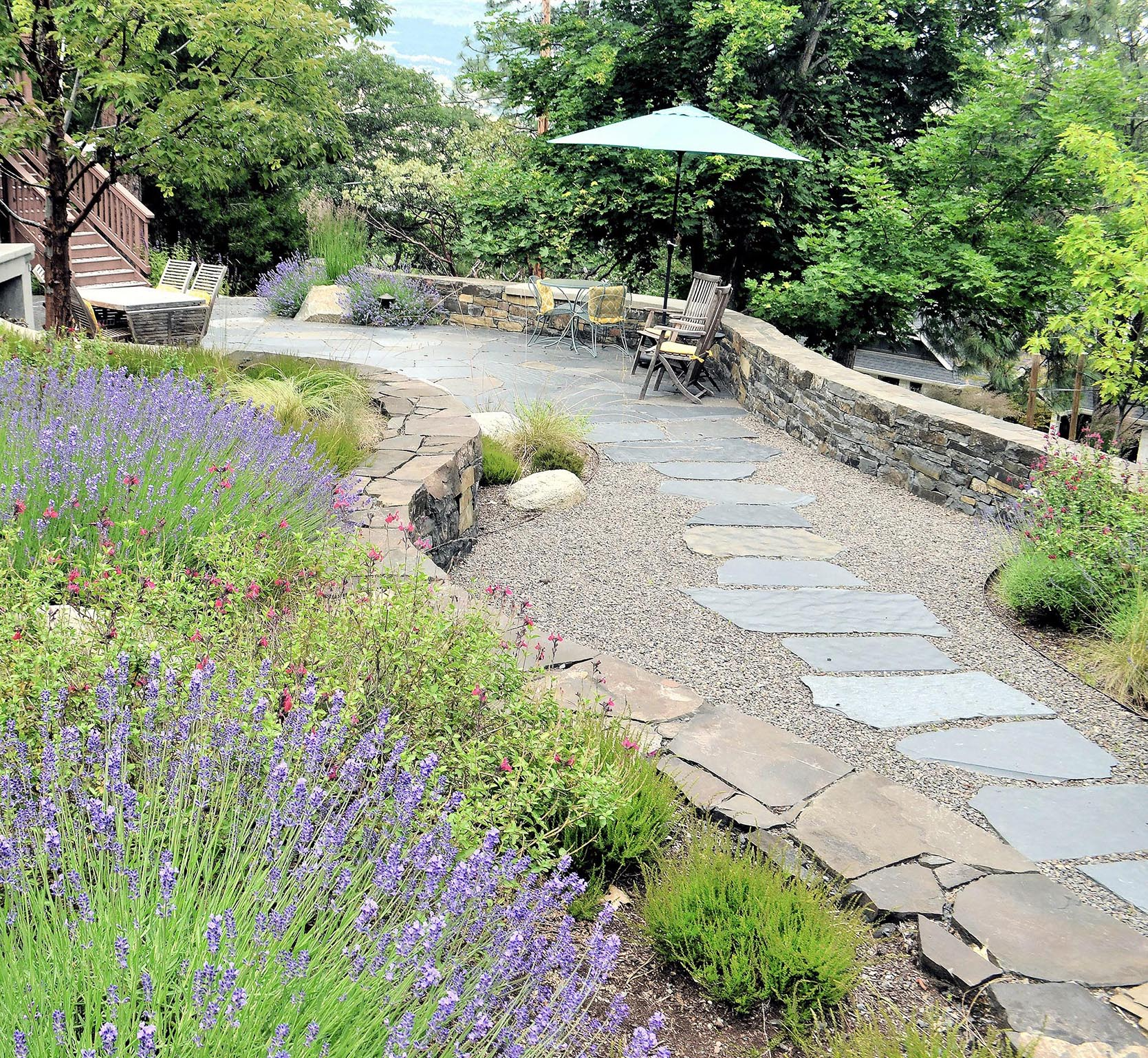 Patio view from bedroom deck looking at lavender blooms and stacked stone retaining walls
