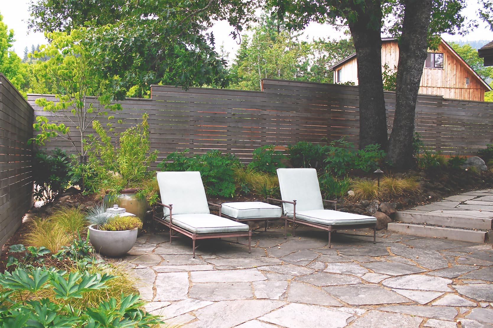 Flagstone Patio + Timber + Gravel Steps + Horizontal Cedar Slat Privacy Fence + Deer-Resistant Perennial Garden + Modern + Seating Area