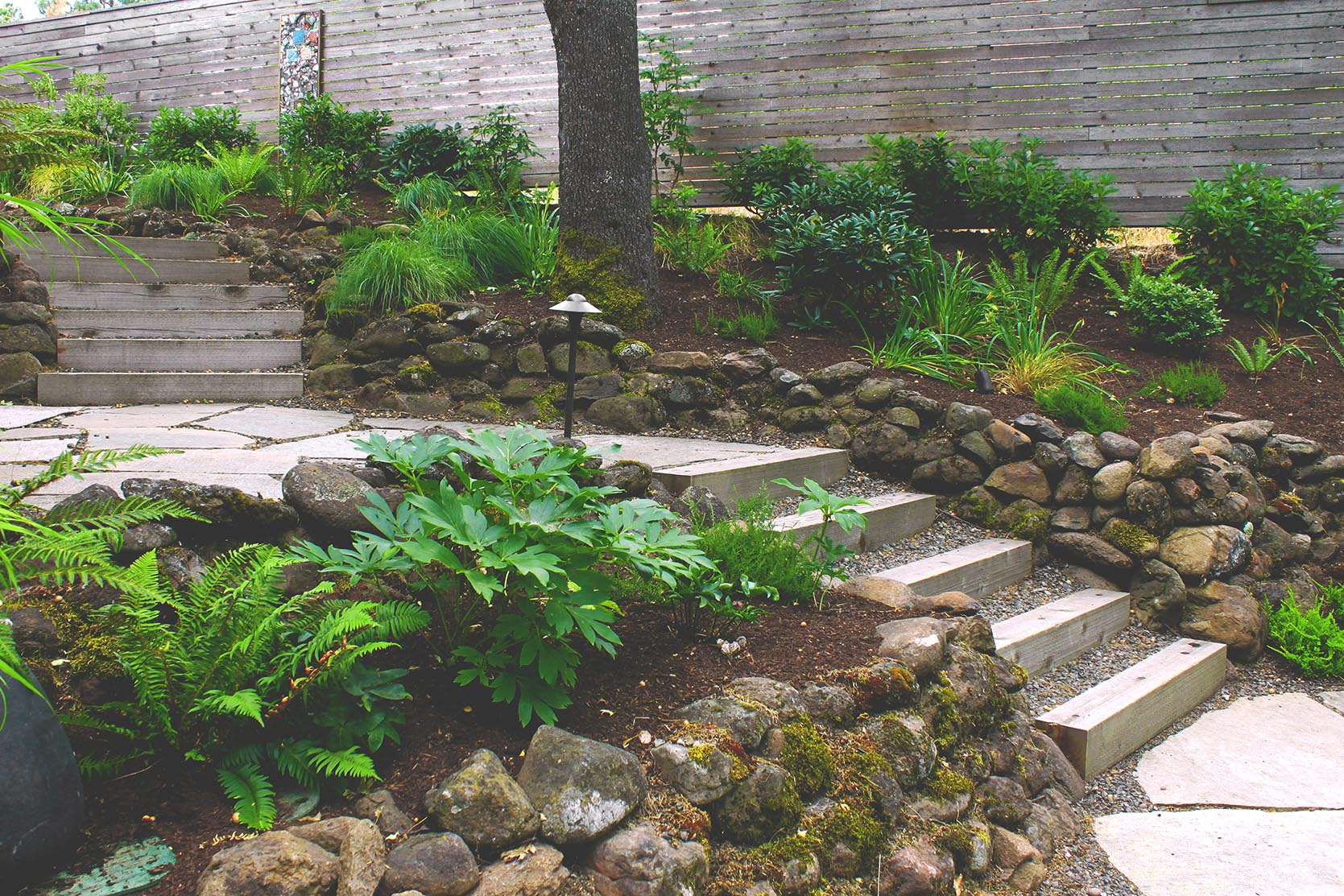 Loose Fit Flagstone Path + Timber + Gravel Steps + Horizontal Cedar Slat Privacy Fence + Deer-Resistant Perennial + Woodland Garden