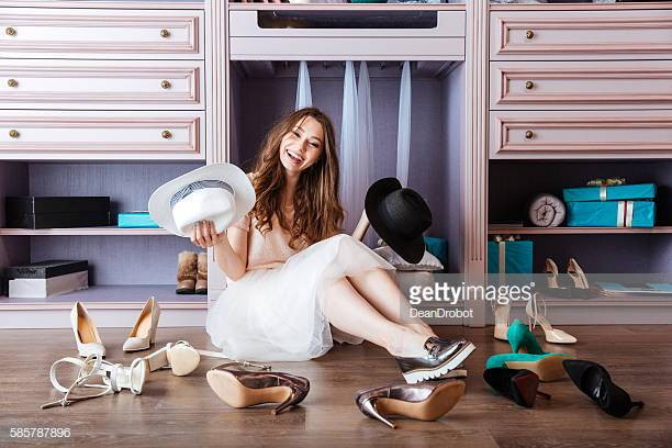 Beautiful young smiling woman in her closet wearing hat