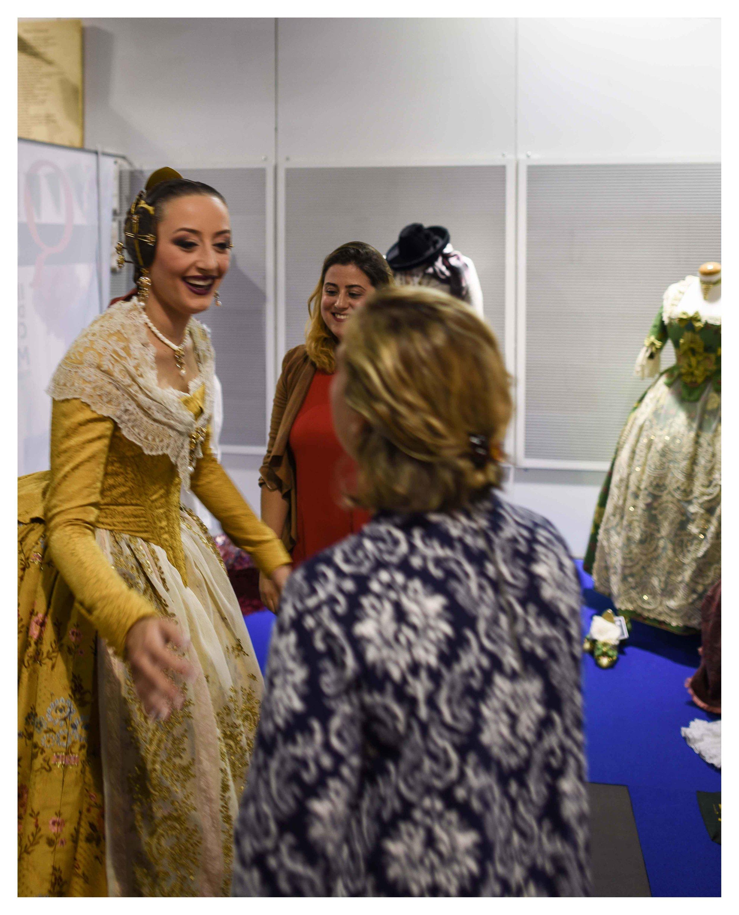 En la imagen, la Fallera Mayor de Valencia 2018, señorita María del Rocío Gil Uncio, saludando a las indumentaristas María y Fátima Aguas de Aguas de Marzo indumentaria.