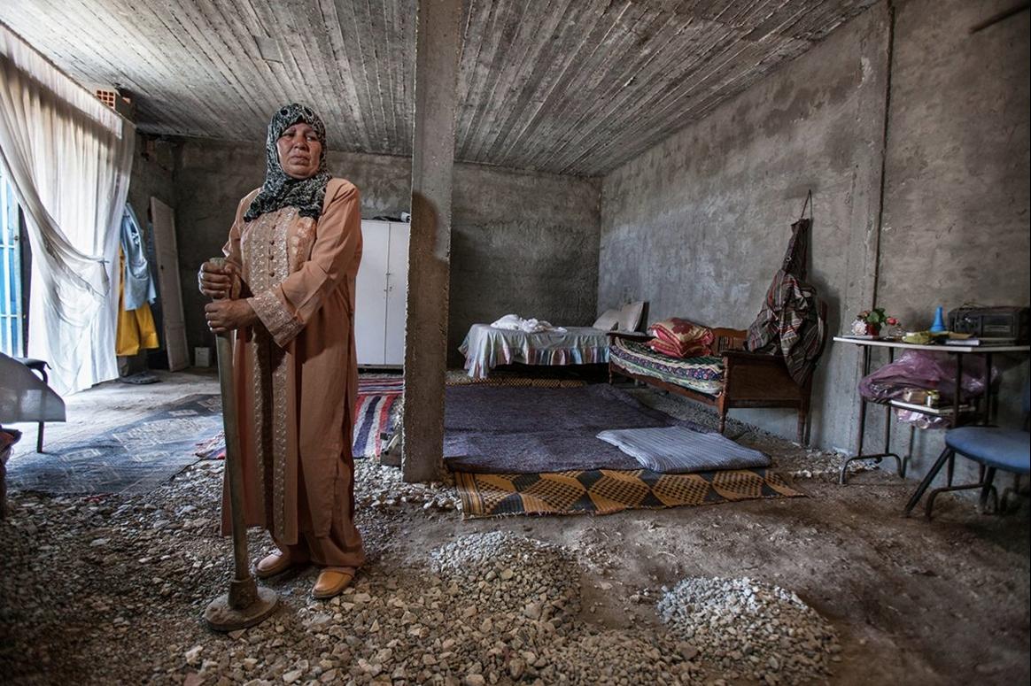 Après avoir été rejeté par l'épouse de son fils, Sahra Bel Rais, du haut de ses 62 ans, entame la construction d'un abri modeste entre deux visites à son mari, hospitalisé à l'hôpital de Bizerte à la suite d'une attaque cardiaque provoquée par le départ de leur fils Aymen Drihmi. Crédit image : Aymen Omrani