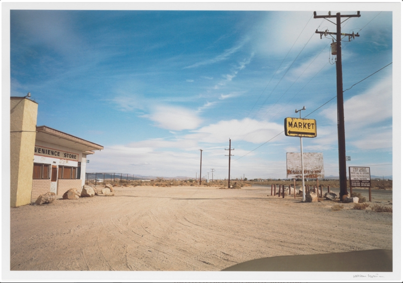 William Eggleston   YELLOW MARKET SIGN AND PARKING LOT   Iris print.   1999-2001.      Signed in ink   William Eggleston   lower right. Edition   3/7  .