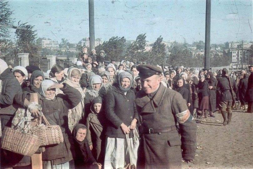 Baby Yar. Le type souriant, au brassard, est un nationaliste ukrainien. Le type de dos, fusil en bandoulière, n'est pas un soldat allemand.