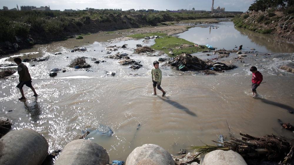 Des enfants se frayent un chemin dans les eaux usées du quartier de Mighraqa, à la périphérie de la ville de Gaza [dossier: Khalil Hamra / photo AP]