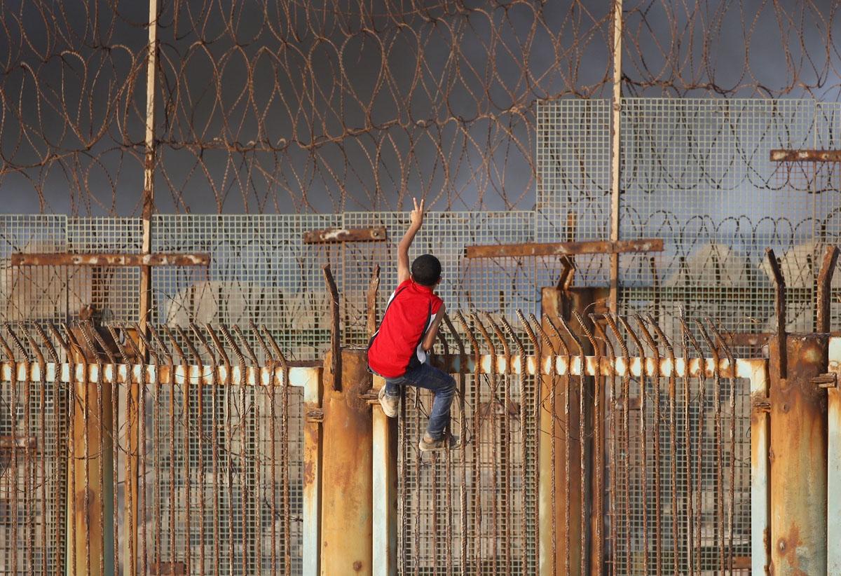 Représente le monde ! Un enfant palestinien est perché sur une des barrières séparant la bande de Gaza du territoire israélien, sur une plage, le 8 octobre 2018. (AFP / Said Khatib). Nous vous recommandons de lire l'histoire de la prise de ces photos dans le blog Making of de l'AFP :    A Gaza, les blessures au corps et à l'âme   .