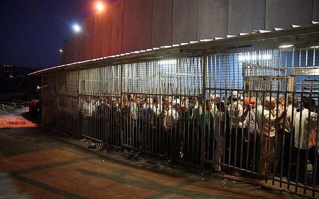 Ceci n'est pas la photo d'une prison, juste ce que doivent endurer tous les jours les palestiniens dans leur propre pays. Des travailleurs palestiniens attendent à un check point à la barrière de sécurité, dans la ville de Bethléem, en Cisjordanie, le 23 août 2010 (Crédit : Najeh Hashlamoun/Flash 90)