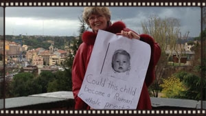 One day it will be a girl!    Dr. Martha Heizen of the International We Are Church Movement (IMWAC) holds a sign: 'Could this child become a Roman Catholic Priest?'  We are working to turn the answer into a resounding 'YES!