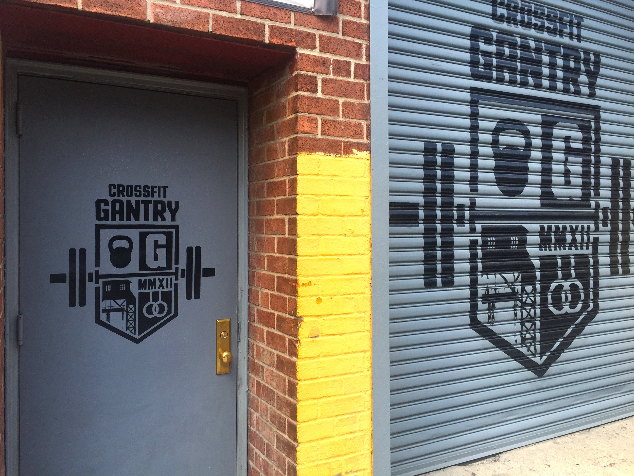 Signs on metal door and rollgate at  CrossFit Gantry  in Long Island City, Queens, NY.