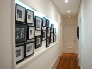 Corredor com spots e iluminação com        no mural de fotos.