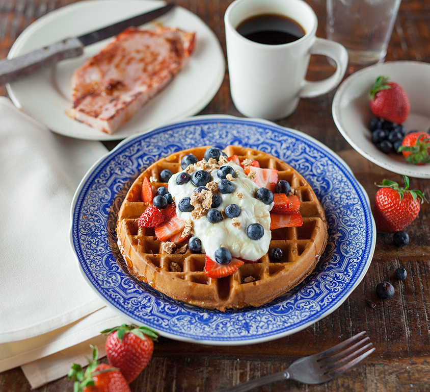 Brunch breakfast with waffle, berries, coffee, and toast at restaurant