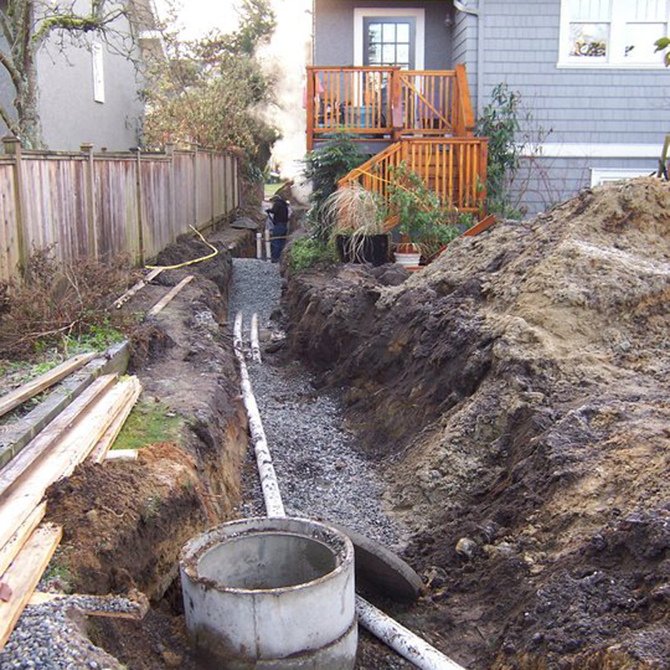 Separate sanitary and storm water sewer pipes connecting a laneway house to the city services in the front yard.