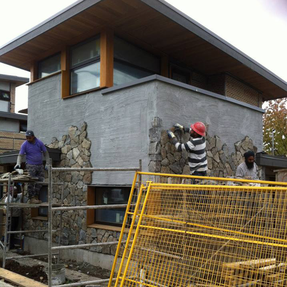 A thin veneer of real stone being applied to the exterior of a lane house.