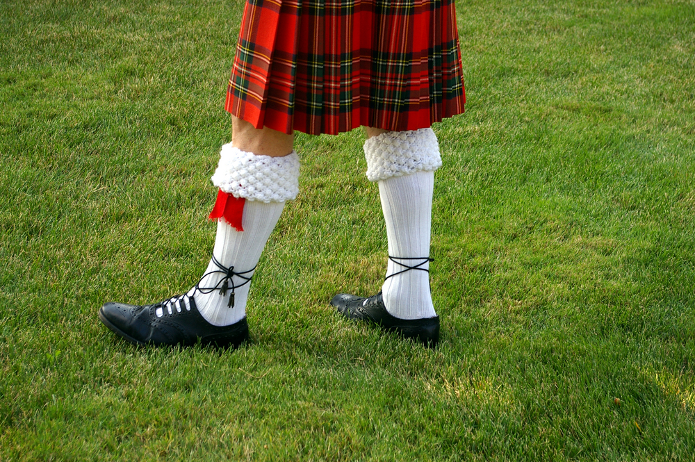 El atuendo se completa con camisa blanca, una chaqueta negra a la cintura, corbatín, medias blancas a la rodilla y  grogues, unos zapatos de atadura.