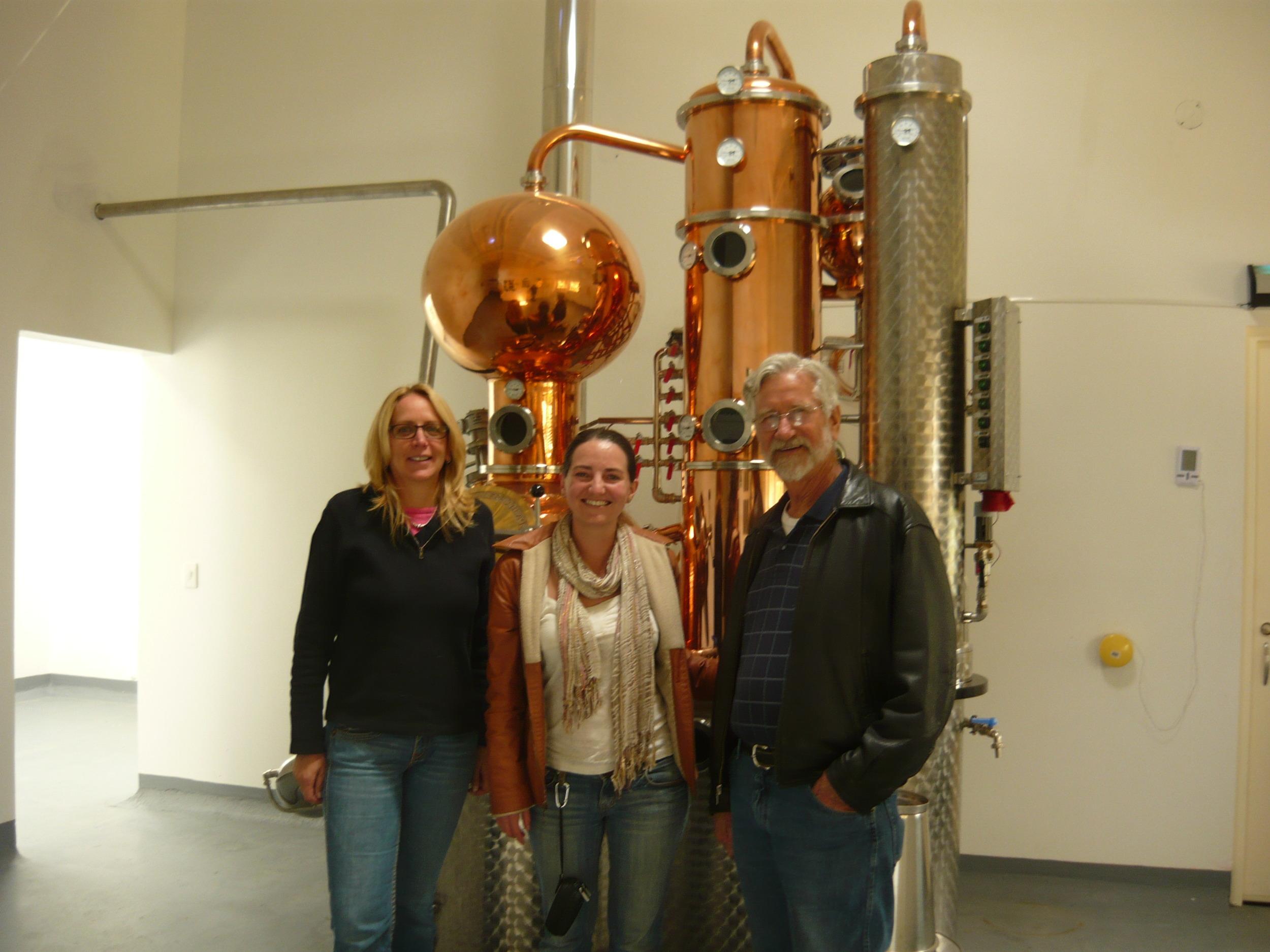Catalina Rugeles en medio de dos de los integrantes de la familia Rode y delante del alambique que produce el  schnapps  colombiano.