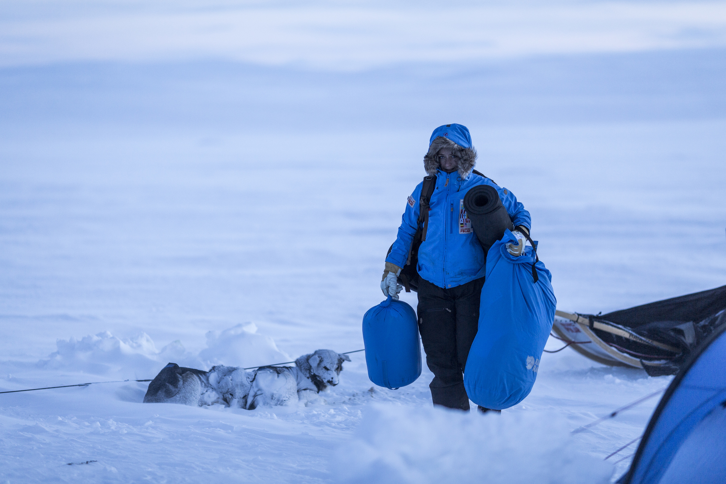 As the sun begnins to set of Råstu, German Fjällräven Polar participant Melanie Ward unpacks her sled and prepares to make camp. (Photo by Håkan Wike for Fjällräven International. All rights reserved.)