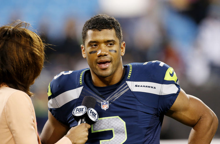 russell wilson looking hot with a microphone near his chest.jpg