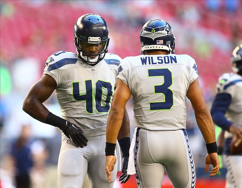 Derrick Coleman looking extremely hot on the field with the hottest quarterback in the NFL with a great ass beside him.jpg