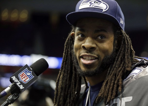 Richard Sherman looking hot wearing a Seahawks hat and jacket.jpg