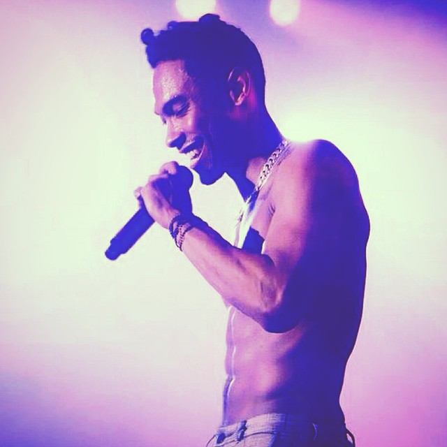 Miguel looking SO hot with no shirt on and a microphone and a purple gradient.jpg