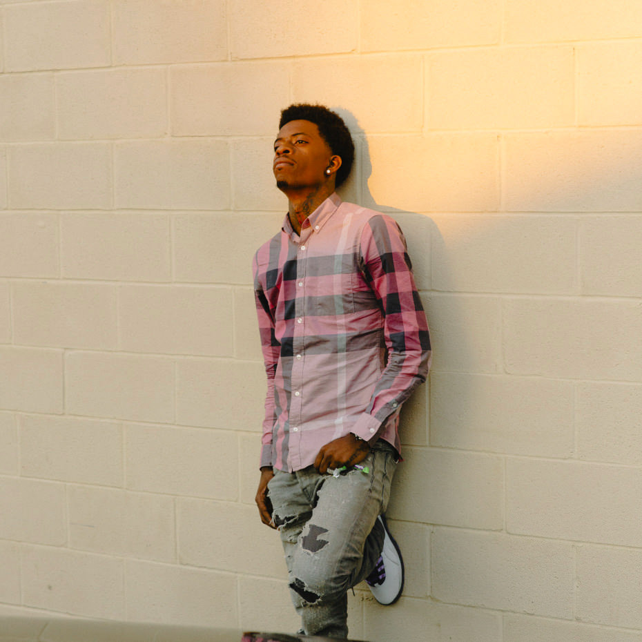 Rich Homie Quan looking stunning as he rests upon a painted cinderblock wall.jpg