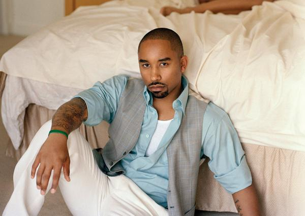 Johnta Austin posing at the end of the bed as he sits on the floor.jpg