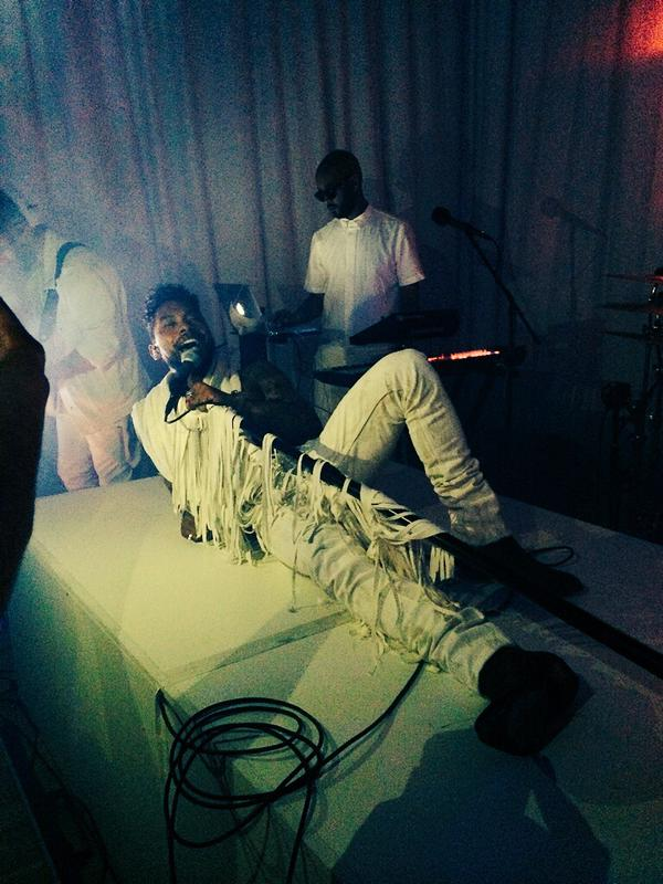 Miguel laying on the runway floor wearing all white during his WILDHEARTEXPERIENCE show.jpg
