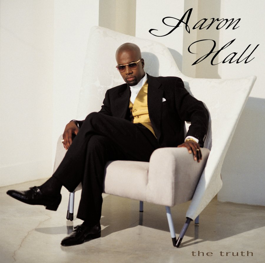 Aaron Hall sitting in a white chair while wearing a suit and looking hot.jpg