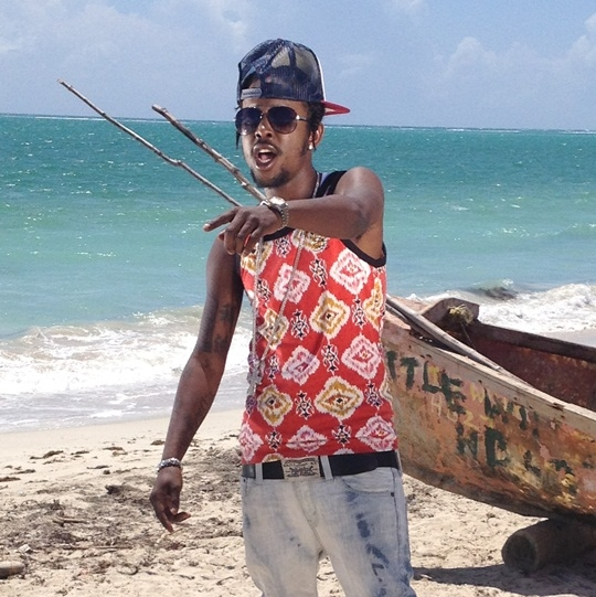 Popcaan wearing a tank top and looking hot on the beach in Jamaica.jpg