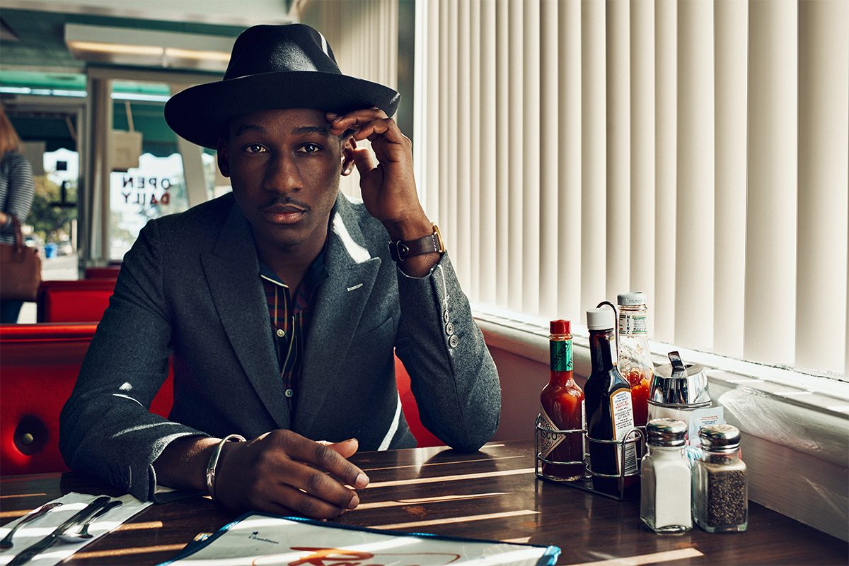 Leon Bridges sitting in a diner trying to figure out what he wants to eat as he looks hot.jpg