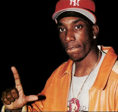 Big L holding up an L with his fingers as he looks hot with a red yankee fitted and a yellow jacket.jpg