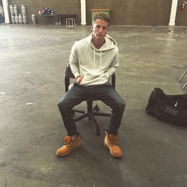 NF sitting in a chair in an empty warehouse.jpg