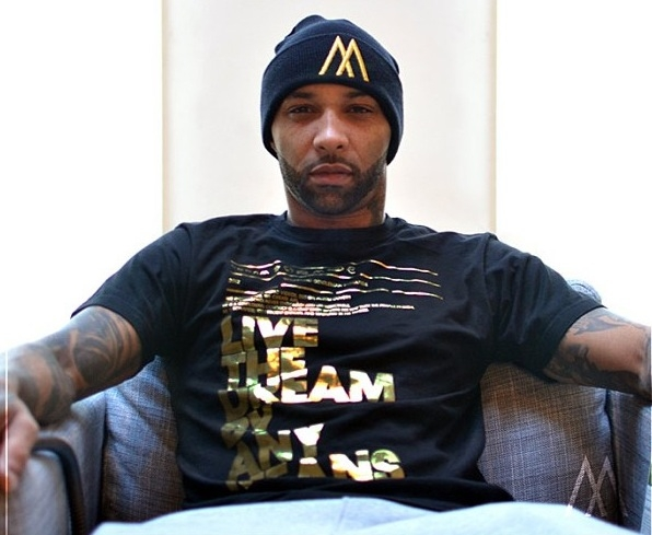 Joe Budden looking gorgeous af in black and gold clothing as he sits in a chair looking hot.jpg
