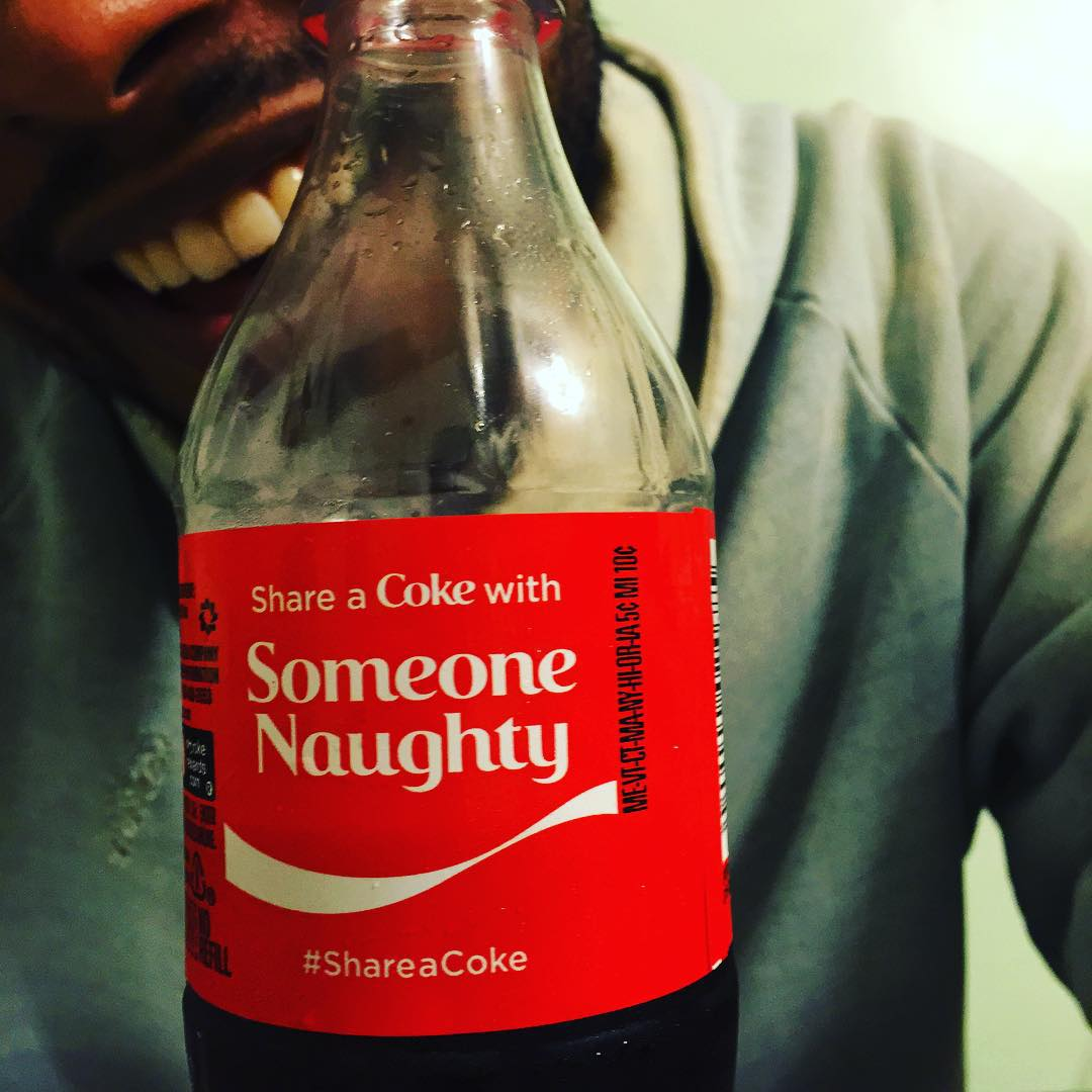Miguel and his gorgeous smile behind a bottle of Coke for Christmas.jpg