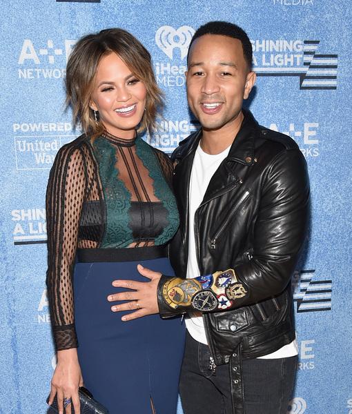 John Legend holding Chrissy Tegien's pregnant stomach as she wears a hideous dress.jpg